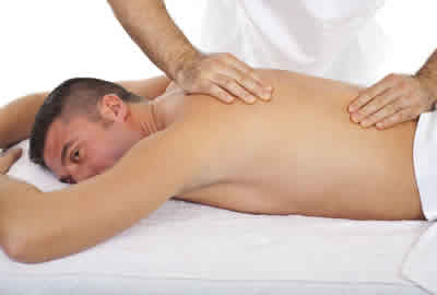 young man with fibromyalgia pain having massage treatment at our Cardiff clinic